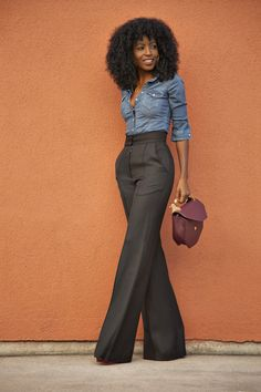 Denim shirt and black, high waist flare trousers.