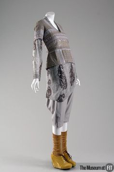 Ensemble (front view) | Dries Van Noten (Belgian, b. 1958) | Belgium, Fall 2007/2008  | Grey and beige linen, ochre cotton, and gold patent leather | Multi-ethnic references are central to the work of Dries van Noten, in part because of his interest in fine craftsmanship. Historically, luxury has often been associated with foreign trade goods, imported from countries such as India with illustrious textile traditions | The Museum at FIT