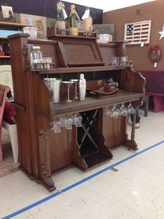 Antique pump organ converted to bar complete with 12 glass rack; bottle storage; and programmable colored lighting.