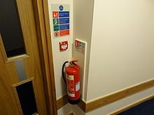 Fire extinguisher - A British fire extinguisher with ID sign, call point and fire action sign.