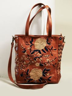El Cosmica Tote | Buttery soft leather tote bag featuring beautiful floral embroidery and bead accents. Zip top closure with zip and slip pockets on the inside and a hidden zip pocket in back. Removable and adjustable long strap and top handles for easy carry.