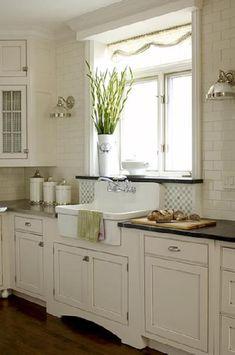 Lovely white modern farmhouse kitchen design with ivory kitchen cabinets black granite counter tops, off-white subway tiles backsplash, farmhouse sink, sconces and glass chrome sconces.