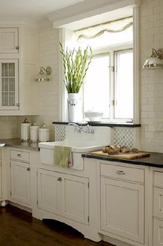 Lovely white modern farmhouse kitchen design with ivory kitchen cabinets black granite counter tops, off-white subway tiles backsplash, farmhouse sink, sconces and glass chrome sconces.