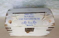 Salty toes, Sandy kisses, Leave your cards for the Mr. & Mrs.  The Sandy Beach Card Box makes the perfect card box and decoration for any wedding, shower or other special occasion. The top of the box is decorated with starfish, shells, sand dollars and saying in the color of your choice (shown in royal blue). Saying is hand painted and can be customized with date. A 9 inch card slot is at the top of the box for guests to drop their cards into the box. The lid opens easily to remove cards at…