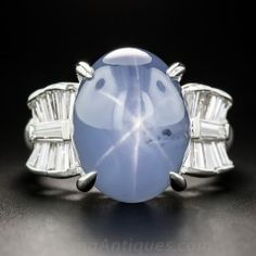 A high-profile cabochon sapphire, weighing 16.50 carats, imbued with a soothing grey-blue hue and shimmering asterism (the star effect). This gem glistens and glows between stylized platinum and baguette diamond bows in this chic and stunning estate cocktail ring reminiscent of the glamorous jewels of Golden Age Hollywood. Currently ring size 5 1/2+.