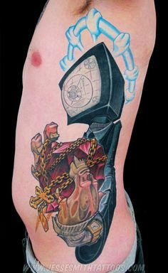 A cartoon graffiti tattoo by Jesse Smith of a character with a TV for a head holding a chrystal heart wrapped in chains « « RattaTattoo