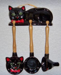 Vintage Shafford black cat with green eyes utensil rack with spoon, funnel, and scoop.