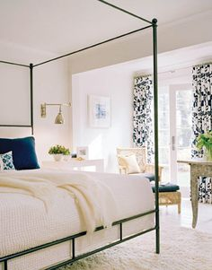 """It's the mix of old and new that gives the master bedroom such great energy,"" says Jodi Macklin, who chose a Niermann Weeks steel four-poster, a farm table in its original paint from Darrell Dean Antiques, a woven armchair and ottoman from Crate & Barrel, and a shag rug from Carpet Impressions. Curtains and shade are in Victorian Hagan's Easy Spring in indigo on white. Urban Archaeology wall light, McGuire laced rawhide stool, Vivi lamp. Bedspread from Abrielle."