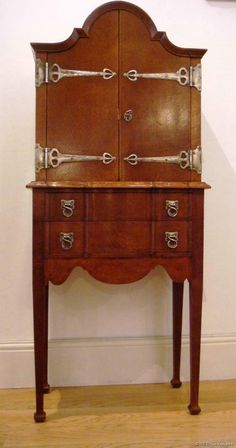 A rare and beautifully proportioned excellent quality Arts & Crafts domed top oak cabinet of compact size; pair of cupboard doors over three drawers, with stunning Rathbone strapwork metalwork  hinges and handles (possibly silvered); the whole very much in the manner of CFA Voysey, for whom Richard Llewellyn Rathbone  did indeed design and make metalwork for.