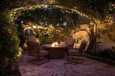 Windlichter und offene Feuerstelle im Garten