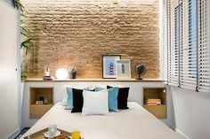 Dormitorio con pared de ladrillo y mueble de obra en el cabecero