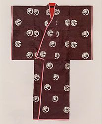 """This is a Heian-style uwagi, in what *looks like* either koki murasaki or koki suou colours.  If it's koki murasaki, then it might would have been worn by an an Imperial woman (or someone depicting one.)  According to the ebook """"Woven Treasures  of Japan's Tawaraya Workshop"""" the woven patterns also can have meanings- for instance, a certain """"...combination of cranes and hollyhocks is reserved  exclusively for the Empress."""" // Ome Kimono Museum, Tokyo"""