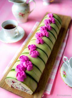 Säkenöivän pinkeillä ruusuilla koristeltu voileipäkakkurulla sisältää poron ja puolukan makuisen täytteen.