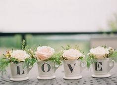 Love use inexpensice coffee cups and stencil Brittany and Trever  on the cups and fill with flowers from the garden store..