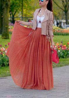 Jupe longue fluide et plissée, couleur corail, sac à main rose, lunettes de soleil, collier sautoir, blouson court en cuir