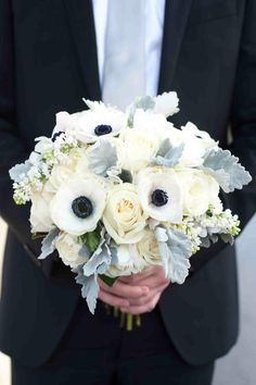 The bride's bouquet featured ivory roses and white anemones with navy blue centers accented with dusty miller. Photography: Donna von Bruening Photographers. Read More: http://www.insideweddings.com/weddings/wedding-planner-genina-ramirezs-southern-celebration/367/