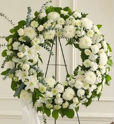 Serene Blessings White Standing Wreath Sometimes, finding the words to show how much a loved one will be missed can be very hard. When you select this standing wreath of all-white flowers, expertly de
