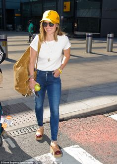 Jet setting: Flying into London's Heathrow Airport from LAX, the 29-year-old cut a stylish figure in a pair of form-fitting mid-wash denims