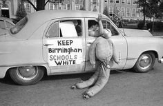 White students in Birmingham, Alabama, drag an African American effigy past West End High School, on September 12, 1963. Two African American girls attended the desegregated school and a majority of the white students were staying away from classes. Police stopped this car in a segregationist caravan in front of the school to caution them about fast driving and blowing auto horns in front of a school. (AP Photo)