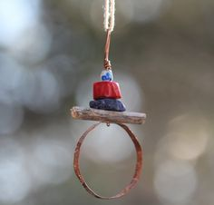 boho pendant comprising ....enamel bead,coral, sodalite gem and driftwood with a handbeaten copper circle.  See this in my shop on Etsy at HammeredandFired.