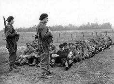Two Polish soldiers of the British Army guard a group of German prisoners in a field in the Netherlands