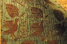 On left, the edge of the cope of Nicholas Alloni, in center, a cope of Lucchese (gilt membrane) brocade with design of birds, palmettes and crescents in gilt membrane and white silk on a blue (now greenish) silk ground. The Orphrey has Kufic characters (detail). N. Italy, 14th c. On right is another cope in Lucchese brocade with design of birds and dogs (detail in final picture), originally gold on red ground that has faded to yellow. N. Italy, 2nd half of 14th c.