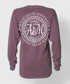 """This longsleeve faded maroon Comfort Colors shirt has a A&M monogram circle on the back with the text """"Texas Aggie Football, Fightin' Texas Aggies"""" The front has a pocket with a block ATM. 100% Cotton."""