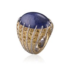 Cocktail ring with purplish blue tanzanite on a mounting with white gold sprigs alternating with yellow gold and diamonds. #TimelessBlue