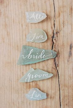 At left: Delicate sea glass in a variety of natural shades and shapes is an understated way to add a nautical touch to your coastal wedding. Collect small pieces and have a calligrapher add guest's