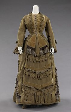 c1875 bustle silhouette dress of silk, cotton and glass. Additional views of this dress, including a pair of button boots can be seen at http://www.metmuseum.org/Collections/search-the-collections/80094026#