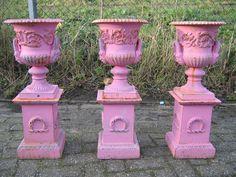 Rose geschilderde gietijzeren franse tuinvazen op pied-de-stalles