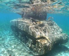 Sherman Tank at Invasion Beach, Saipan. Note that the hatches are still opened from the escaping U.S.crew.