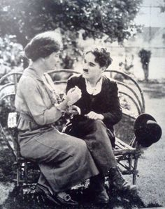 Charlie Chaplin talking to a 'common person' while sitting on a park bench.