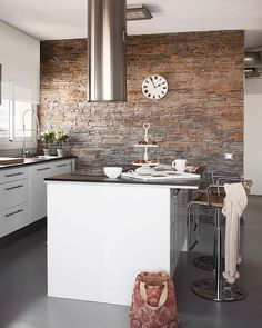 Cocina en blanco y con muro de piedra en gris.