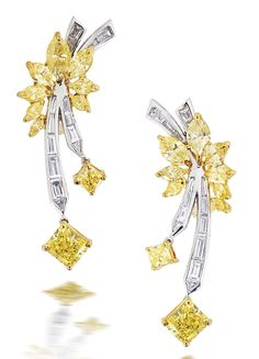 A pair of coloured diamond and diamond earrings Each flowerhead forming clusters of marquise-cut diamonds of yellow hue, the stems inlaid with baguette-cut diamonds, suspending four radiant-cut diamonds of yellow hue, the largest weighing 1.04 and 1.01 carats, mounted in platinum and 18k gold