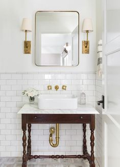 A brass curved vanity mirror hangs between antique brass sconces from a white powder room wall accented with white subway backsplash tiles finished with light gray grout.