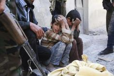 Children react next to the body of their mother after she died what activists said where explosive barrels thrown by forces loyal to Syrian President Bashar al-Assad in the Al-Andhirat neighbourhood of Aleppo February 22, 2014.  REUTERS/Hosam Katan