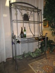 "Price: $249.99 | Item #: 48231  Glass and metal bakers rack. This piece has wine bottle and glass storage, along with two glass shelves for additional storage space. Measures 43""wide x 18""deep x 76""high. At posting, we have the matching dining set."