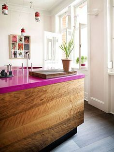 Hot pink counters are offset by traditional wood cabinetry in a kitchen from Bungalow via | Apartment Therapy AND LOOK AT THE CAMPBELL'S SOUP LIGHTS!