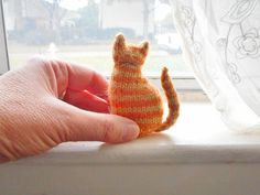 This pattern is a tiny version of my regular Window Cat pattern.It's 3 inches tall, worked in the round, and all in one piece except for the tail. The only seaming is to attach the tail to the side of the body.I've tried it with various yarn sizes from fingering to DK weight, and used size US 1 dpns with all of them. They all came out great.Attach a little cord and make some tree ornaments for the cat lover in your life! :-)