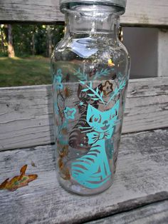 A sweet vintage clear glass apothecary jar featuring turquoise and gold cats…  offered by Ruby Lane shop Saltymaggie's Treasures