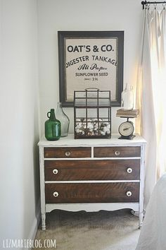 Gray/wood dresser with DIY vintage towel art. Scale with vintage glass bottles on display & a terrarium filled with cotton.