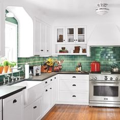 Kitchen inspiration: white cupboards with ebony handles and black countertops, hardwood floors, and stunning emerald tiles for the backsplash and part of the walls