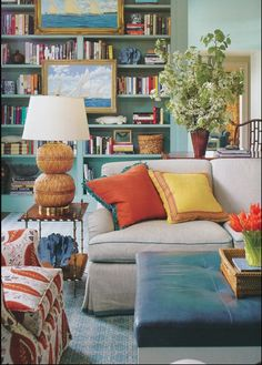 In no particular order, the yachting paintings hung on the bookshelves, the styling of the bookcase, the pillows, the upholstered chair, the sofa piping, the blue coral, the end table.  By Katie Ridder.