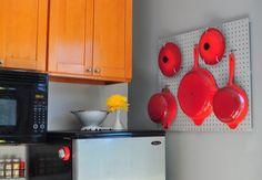 Eu tenho que dizer que uma coisa que mais me irrita na minha cozinha é não ter um espaço bom para as minhas panelas. Elas ficam bagunçadas embaixo da pia, uma dentro da outra, uma bagunça só. Por isso eu adorei essa ideia de pendurar as panelas num painel furadinho com ganchos, tipo ferramentas numa oficina.