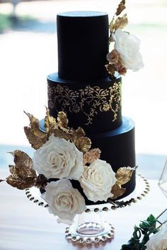 black and white wedding cakes black cake with golden patterns decorated with white roses with golden leaves kristi sneddon photographer via instagram