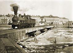 Höyryveturi ylittämässä halki torin kulkevan Satamaradan kääntösiltaa. Taustalla näkyy Pohjoiseslanadin reunustaloja. Signe Brander 1907.