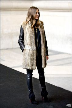Olivia Palermo kept warm at the Armani show in Paris wearing a long fur vest.
