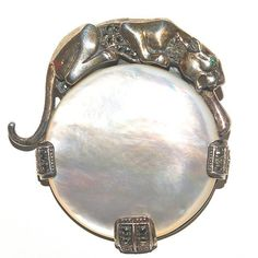 Sterling silver and mother-of-pearl panther brooch by Ari D Norman. It can also be worn as a pendant.  This beautiful high quality brooch was inspired by the Duchess of Windsor's jewellery of the 1930's.  It is fully hallmarked and is also stamped Ari 1990. The panther has lovely green eyes and is set with marcasites.  This is a special brooch that really makes a statement!