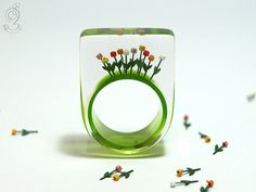 Tulips from Amsterdam springlike flower by GeschmeideUnterTeck: On a green ring grow ten colourful plastic mini-tulips up to the sky (red, orange, yellow, pink and white).  The ring is very light and despite of the size extremely good to wear...always an eye-catcher.